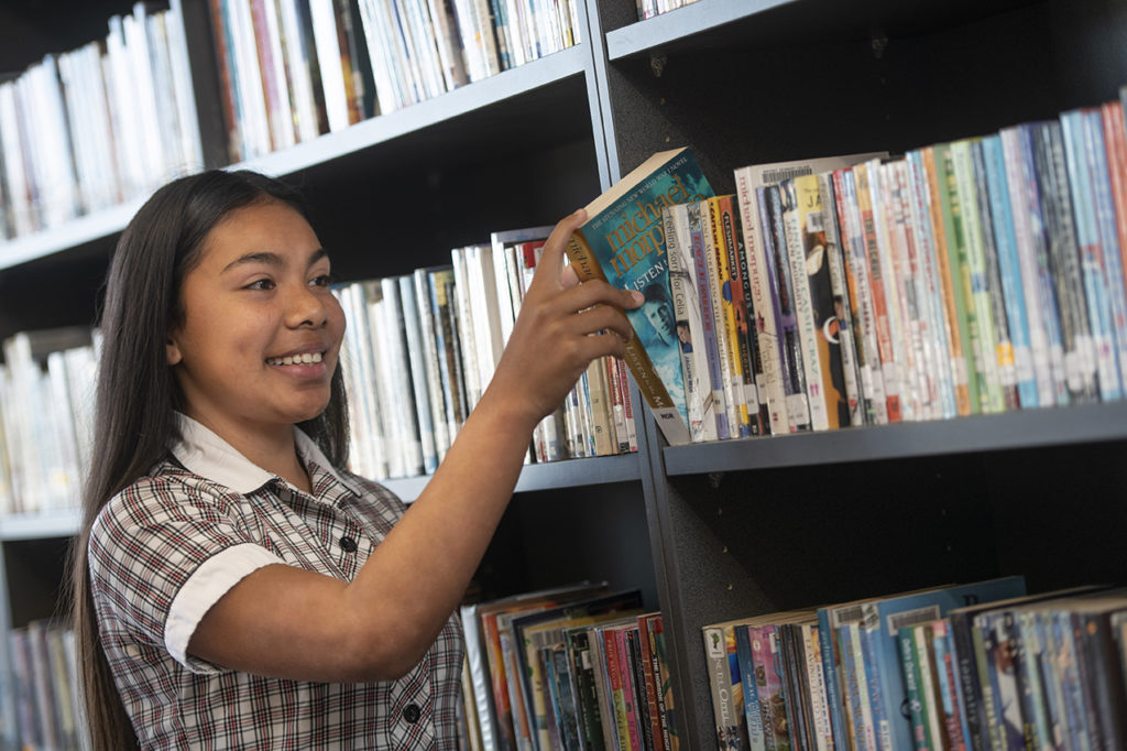 Student selecting book from library